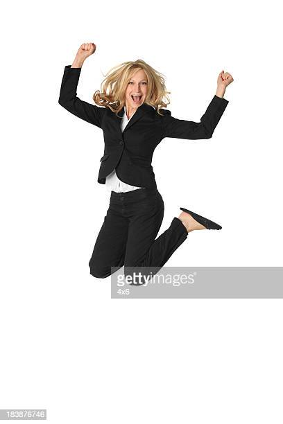 Blond businesswoman jumping for joy