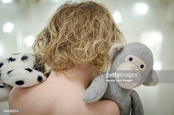 blond child cuddling soft toys