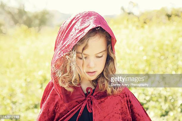 Blond curly hair girl in red cape