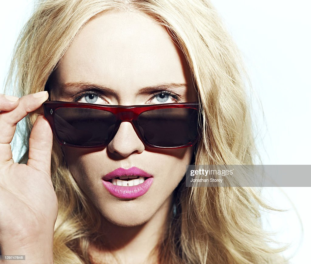 blond female looking over sunglasses holding frame : Stock Photo