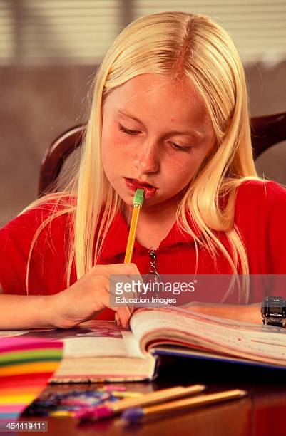 Blond Girl Age 10 Concentrating On Her Homework