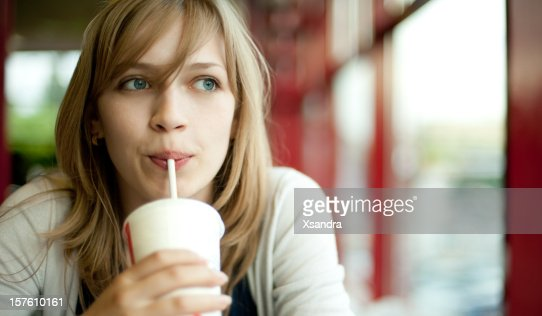 A blond girl drinking a cold beverage while looking outside