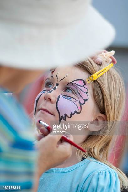 Blond girl getting a butterfly painted on her face