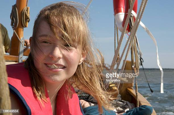 blond girl in life jacket on a sailing boot
