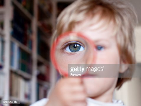 Blond girl looking through magnifying glass, close-up : Foto de stock