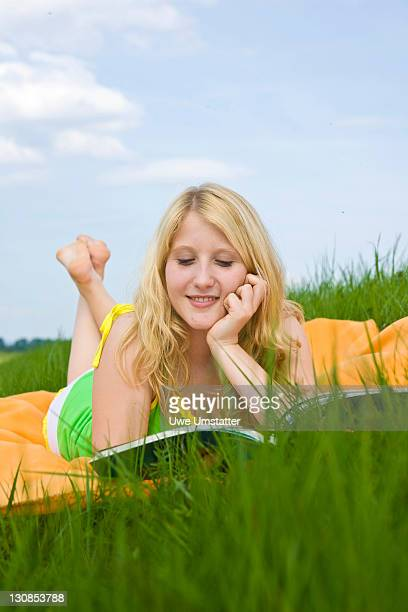 Blond girl lying on a blanket in the grass and reading a book