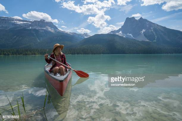 Blond girl on red canoe in Canada