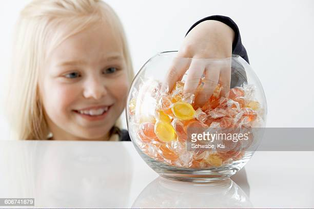 Blond girl reaching into a sweet jar