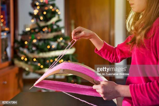 Blond girl with a home loom next to the Christmas tree