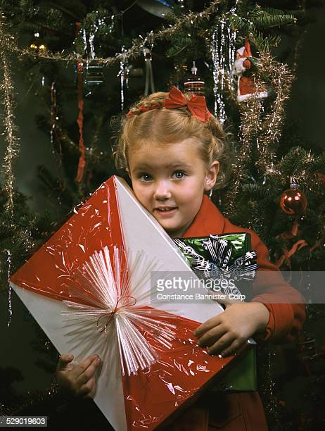 Blond girl with braid and red ribbon in hair holding red and white christmas present in front of christmas tree