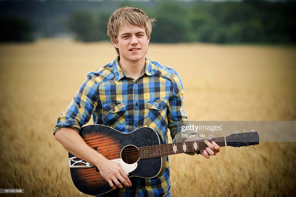 Blond man in checkered shirt playing guitar in country field : Stock Photo