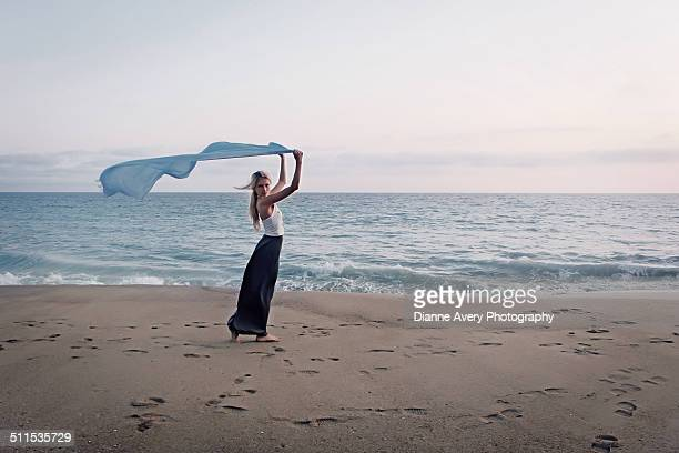 Blond teen holding blue scarf at the beach