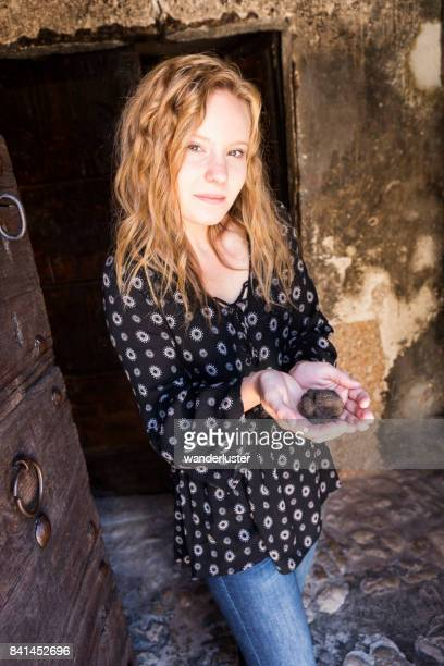 Blond teenage girl holds a large black truffle in her hands, Abruzzo, Italy, Europe