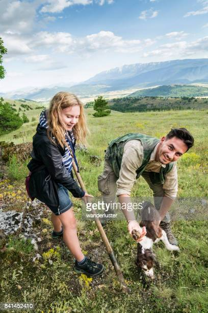Blond teenage girl uses the vanghella tool to assist the Springer Spaniel dog dig out truffles as the male hunter in his 20's watches on a summer day, Abruzzo, Italy, Europe