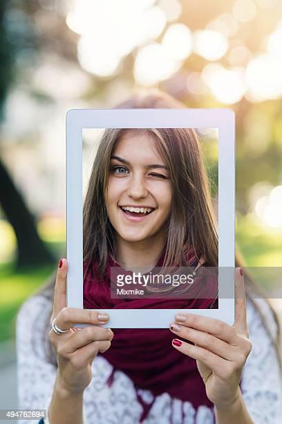 Adolescente blonde fille tenant une tablette avec un selfie