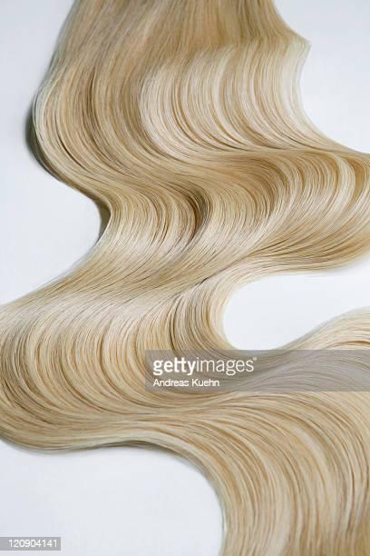 Blond wavy hair on white background.