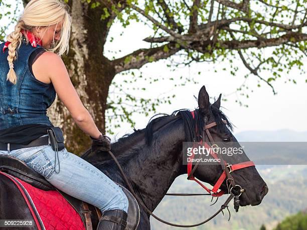 Blond woman and black horse