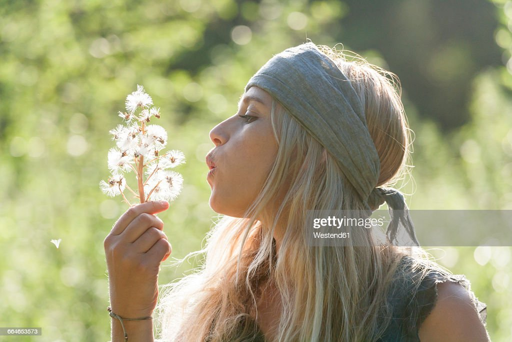 Blond woman blowing seeds of an umbel into the air
