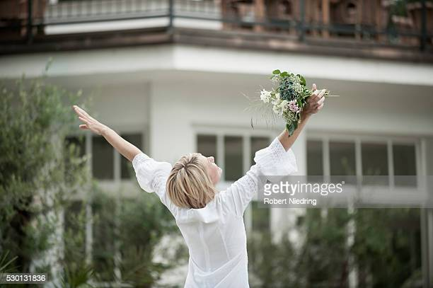 Blond woman dancing elated holding wedding bouquet