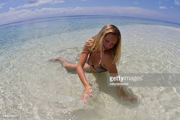 Blond woman enjoying the crystalline water of a lagoon