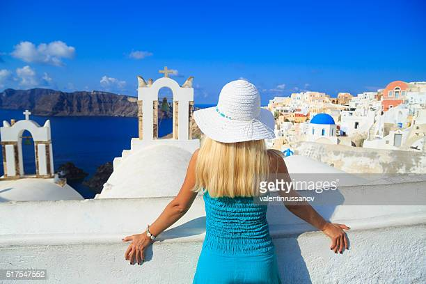Blond woman enjoying the volcano view of Santorini