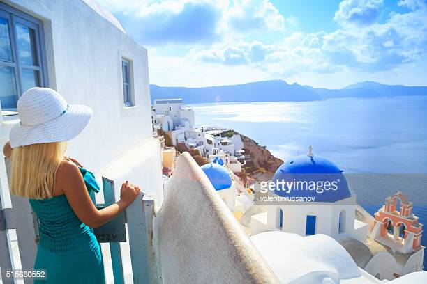 Blond woman in front of town Oia at Santorini