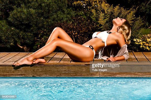 Blond Woman in White Bikini Posing at Pool