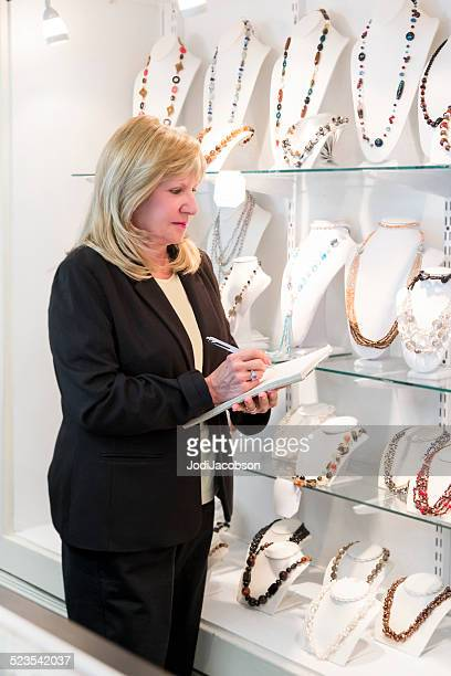 Blond woman jewelry store owner checking inventory on display