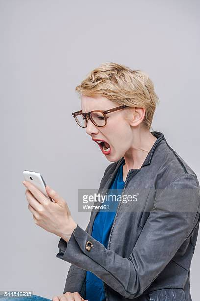 Blond woman looking at her smartphone screaming