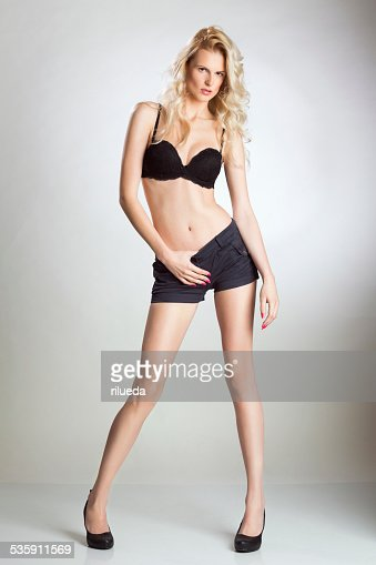 Blond woman posing in bra and hot pants : Stock Photo