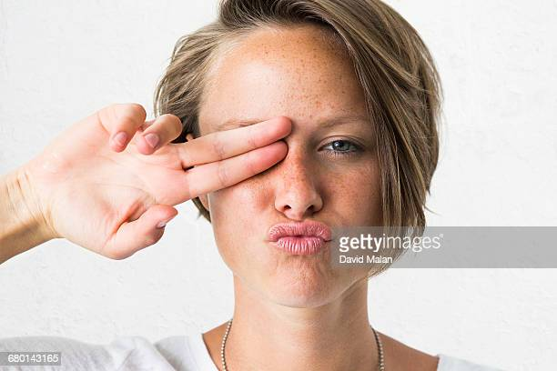 Blond woman putting two fingers over her eye.