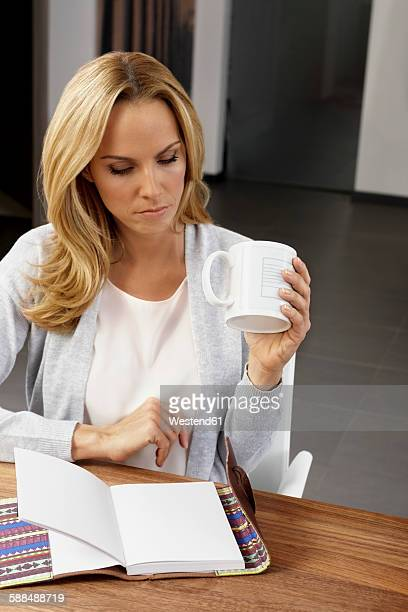 Blond woman sitting at table reading a book and drinking coffee