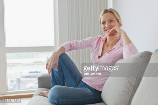 Blond woman sitting on sofa, smiling