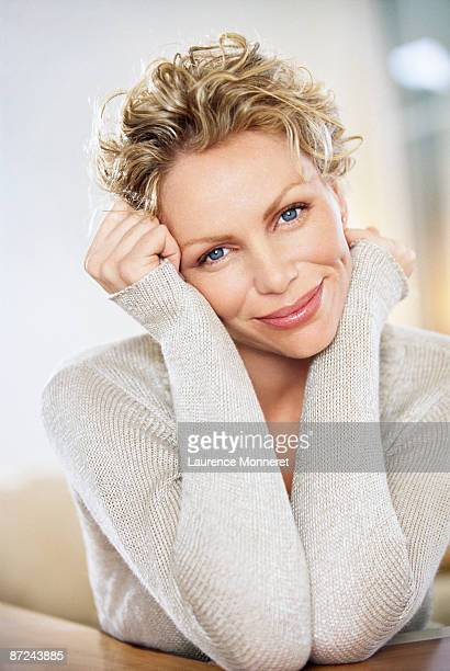 Blond woman smiling face leaning on wrists