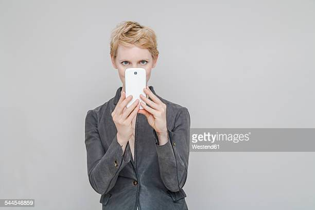 Blond woman taking a photography with smartphone in front of grey background