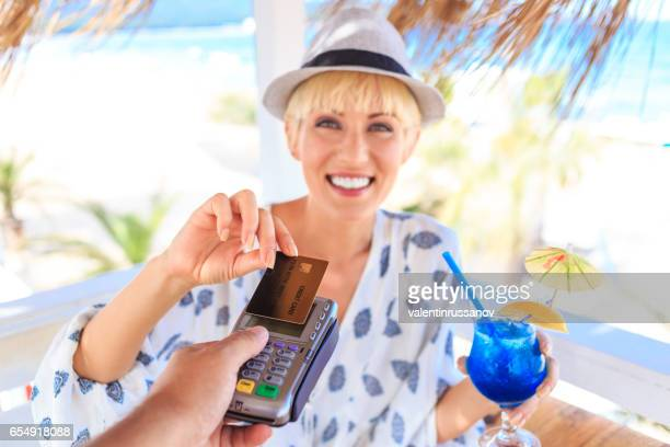 Blond woman using credit card for contactless payment on beach