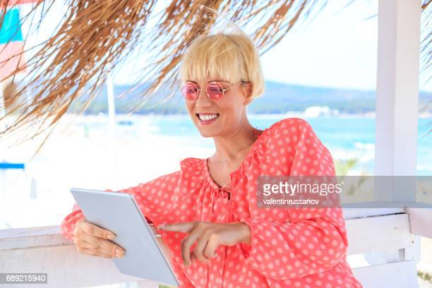 Blond woman using tablet in beach bar