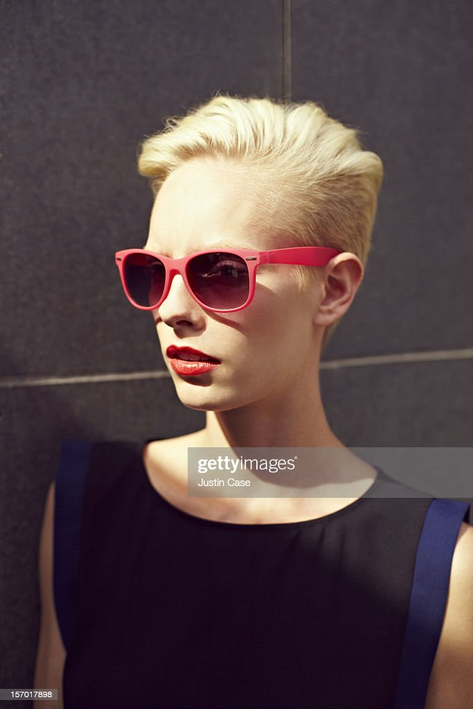 A blond woman wearing sunglasses : Stock Photo