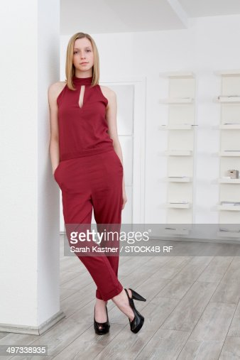 Blond young woman leaning against wall