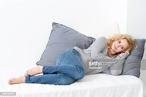 Blond young woman lying on couch
