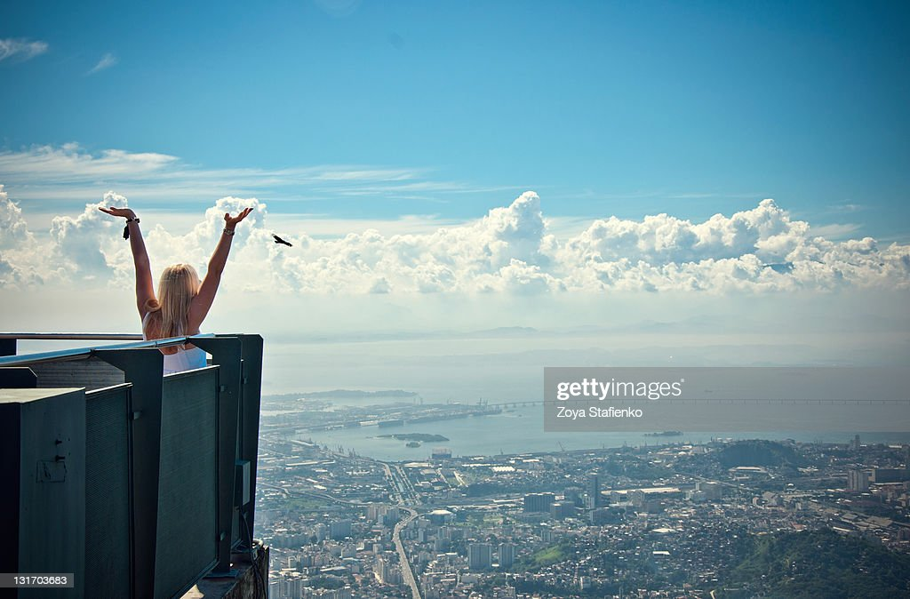 Blond young woman with hands up over city : Stock Photo