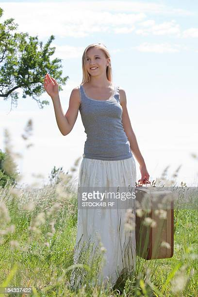Blond young woman with suitcase in field