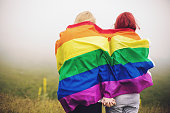 Blonde and redhead woman wrapped in rainbow flag