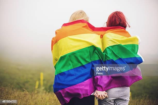 Blond und rotes Haar-Frau mit Regenbogen Flagge