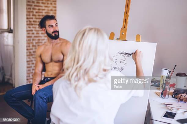 Blonde artist taking skatches of her handsome model