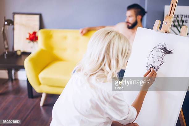 Blonde artist taking skatches of her handsome model