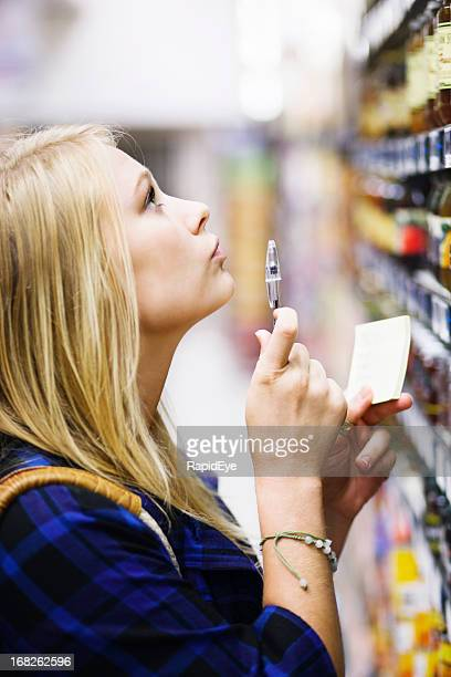 Blonde babe checks the choices on supermarket shelf