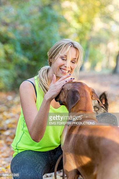 blonde beauty in her 30s strokes her brown dog