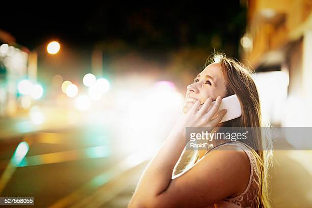 Blonde beauty lit by street lights chats, smiling, on smartphone