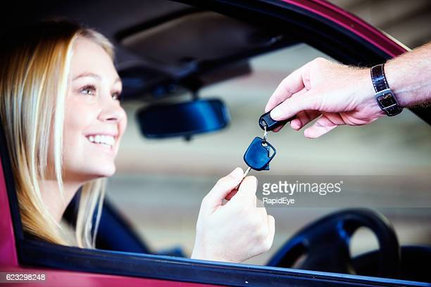 Blonde beauty smiles in delight, receiving keys to new car